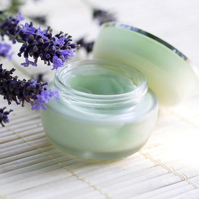 Lavender moisturizer on bamboo with purple lavender flowers in the background. Lavandula anugustifolia
