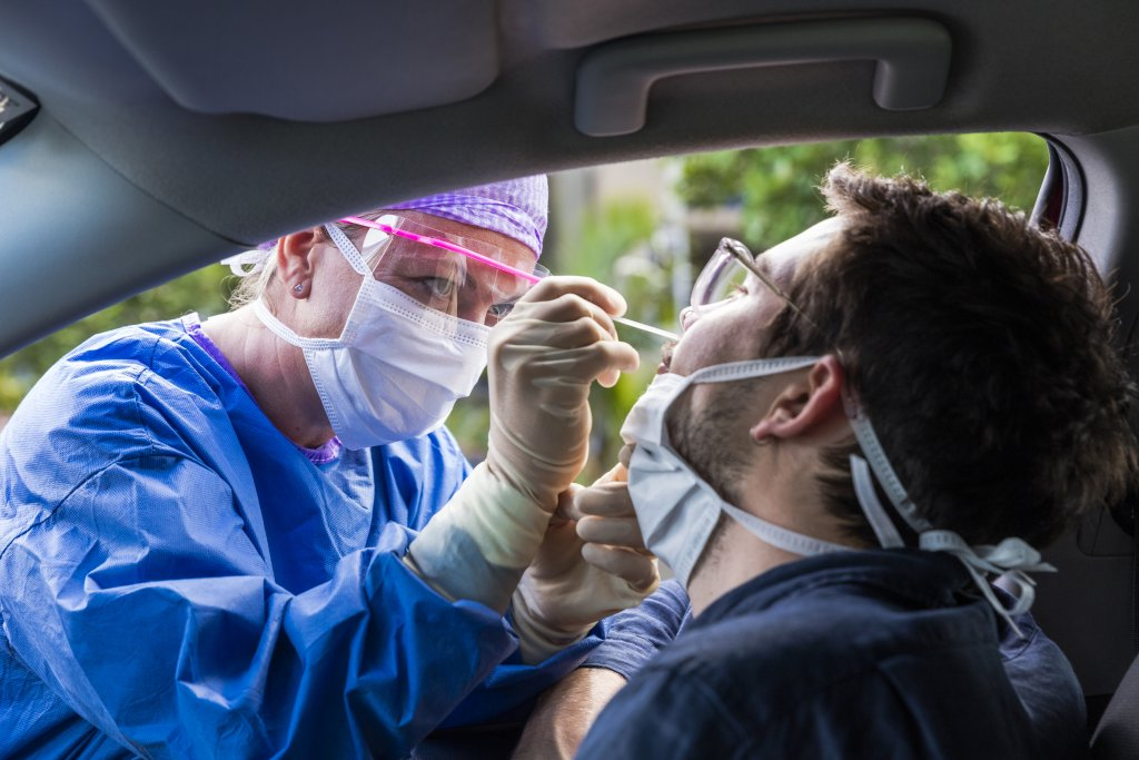 doctor taking COVID nasal swab from a driver