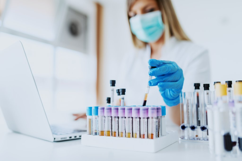 lab assistant holding test tube with blood sample